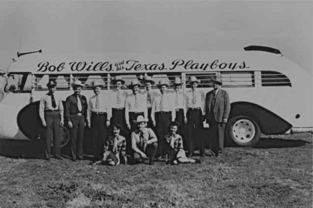 Bob Wills and his Texas Playboys standing by their bus